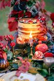 Wedding cake in autumn with fruits. Pomegranate and autumn leaves royalty free stock images