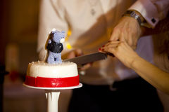 Wedding cake with bears and knife in hands of bride and groom Royalty Free Stock Photo