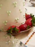 Wedding cake being served. Wedding cake detail, with strawberries and serving utensil Royalty Free Stock Image