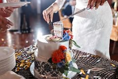 Wedding cake with flowers on table. Bride and groom cut sweet cake on banquet in restaurant. stock photo