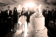 Wedding cake. A big wedding cake in a ballroom with guests royalty free stock photography