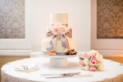 Wedding Cake. White wedding cake at a wedding reception and bouquet with Roses, Dusty Miller, Ranunculus Royalty Free Stock Photos