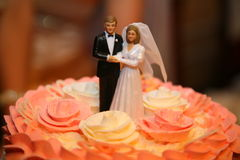 Wedding cake with a bride and bridegroom and blurred gifts in the background. Wedding cake with pink rosettes and a sculptural group - the bride and groom royalty free stock images