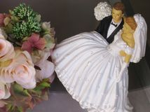 Wedding cake bride and groom figures with bouquet. Elegant wedding cake statuettes with pink floral bouquet Stock Images