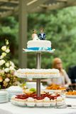 Wedding cake. With bride and groom figures sitting on top. Tiered cake stand royalty free stock photos