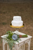 Wedding cake and brides bouquet. On table Royalty Free Stock Photo
