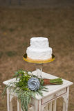 Wedding cake and brides bouquet. On table Stock Photography