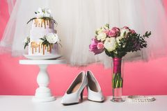 Wedding cake on cake stand with white dress and bouquet. On pink stock photos