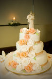 Wedding Cake and Candle. A wedding cake with flowers and lit candle in the background Stock Image