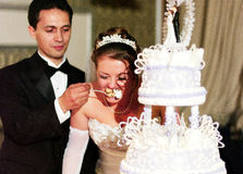 Wedding Cake Ceremony. Bride and Groom feeding each other cake Royalty Free Stock Image