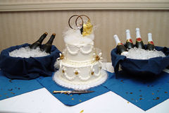 Wedding Cake with Champagne. A table with a wedding cake and two buckets filled with champagne bottles royalty free stock photo