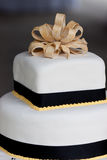 Wedding Cake. Close up of Black, white and yellow wedding cake with fondant and yellow trim and bow Stock Images