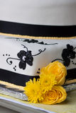 Wedding Cake. Close up of Black, white and yellow wedding cake with fondant and yellow trim and flowers Stock Image