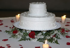 Wedding Cake Closeup by Candlelight. Closeup of a white wedding cake surrounded by rose petals and lite by candlelight Royalty Free Stock Image