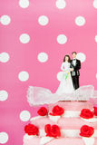 Wedding cake with couple on pink background Royalty Free Stock Photo