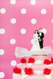 Wedding cake with couple on pink background Royalty Free Stock Photo
