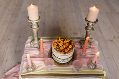 A wedding cake decorated with kumquat, sea buckthorn stands on a table with a pink cloth surrounded by candles. Top view. A wedding cake decorated with kumquat Stock Photography