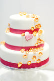 Wedding cake decorated with pink rose flowers and hearts . Stock Photography