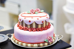 Wedding cake decorated with pink rose flowers and hearts . Royalty Free Stock Image