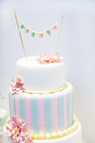 Wedding cake decorated with pink rose flowers and pearls. Stock Photos