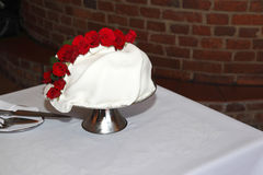 Wedding cake. Decorated with red roses Royalty Free Stock Images