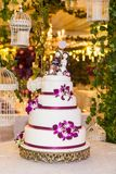 Decorated wedding cake in the event room. Wedding cake on the decorated table with figures that represent the couple, on the cake Stock Photography