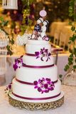 Decorated wedding cake in the event room. Wedding cake on the decorated table with figures that represent the couple, on the cake Stock Image