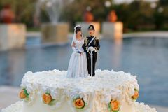 Wedding cake with the decoration of the bride and groom on top Stock Photos