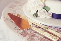 Wedding cake. Decorative wedding cake with gold serving utensils stock photography