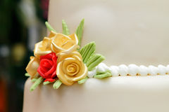 Wedding cake detail. Round wedding cake covered in white rolled fondant and decorated with brightly colored roses Royalty Free Stock Photo