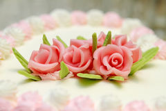 Wedding cake detail. Wedding cake covered in white rolled fondant and decorated with brightly colored roses Royalty Free Stock Photos