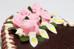 Wedding cake detail. Wedding cake covered with chocolate and decorated with brightly marzipan colored roses Royalty Free Stock Photography