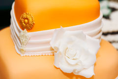 Wedding cake detail. Wedding cake covered in white rolled fondant and decorated with marzipan flowers stock images