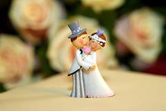 Wedding cake dolls closeup. With roses on background Stock Photos