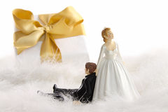 Wedding cake figurines with gift on white Royalty Free Stock Photography
