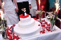 Wedding cake with fireworks. An elegant white wedding cake with fireworks and red roses on a table royalty free stock photos