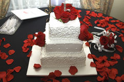 Wedding cake and flowers. Wedding cake surrounded by roses and rose petals Royalty Free Stock Photo