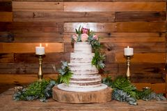 Wedding cake with flowers and candles. Wedding cake and celebration with ferns and flowers and candles on wooden tray royalty free stock photos