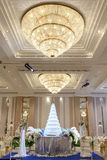 Wedding cake and flowers  decorations with chandelier on ceiling. Royalty Free Stock Image