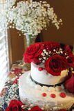Wedding cake and flowers. Red flowers on a wedding cake with white flowers in the background Stock Images