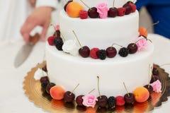 Wedding cake with fruit. The couple cut the wedding cake Royalty Free Stock Photo