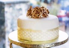Wedding cake with golden roses Stock Photos