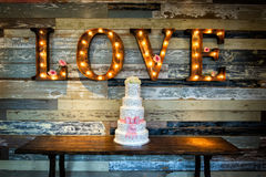 Wedding Cake with Love. Image of a wedding cake with the word love as sinage on a rustic background Stock Image