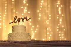 Wedding Cake with LOVE Topper. A simple white wedding cake with the word love written in sparkling gold letters on the top, with white twinkling lights and