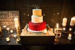 Wedding cake with Mr and Mrs Topper. Red and white icing royalty free stock images