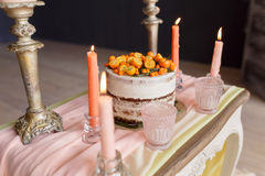 A wedding cake with orange berries and candles stands on the table. Close-up photo, focus on the cake. A wedding cake with orange berries and candles stands on Royalty Free Stock Images