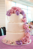 Wedding cake with pink and purple flowers. Three tiered wedding cake with pearls and pink roses and purple flowers Stock Photos