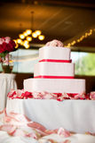 Wedding cake with roses. A Beautiful three layered wedding cake sprinkled with roses Stock Photography