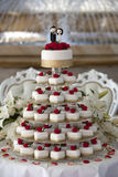 Wedding cake. With roses and groom and bride figures. Bridal chairs and fountain in background royalty free stock photos