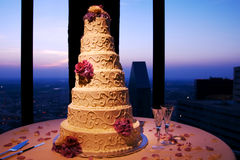 Wedding Cake Skyline. An elaborate wedding cake on display in a Dallas high rise with the dusk skyline in the background.  The focus is on the detail of the cake Stock Photography